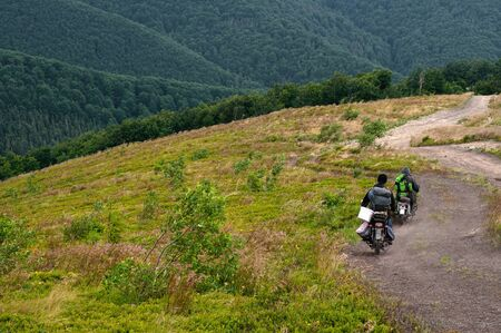 Mountain landscape. Blueberry pickers in the mountains of the Carpathians, covered with green bilberry, on motorbikes ride on a country road. People and their traditions.  No faces. Photo from the back.