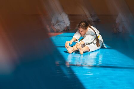 A teenager girl with a yellow belt in karate class is doing stretching. Beautiful morning light. Oriental martial arts. Children's training.