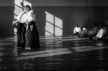 the city of Minsk, Belarus - June 1, 2019. Seminar on traditional Aikido. The teacher Makoto Ito shows reception.  Traditional form of clothing in Aikido. Black and white image.