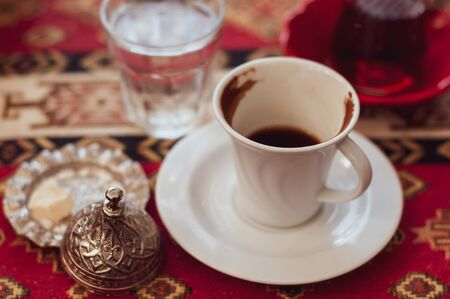 Authentic white cups with black coffee on the table in a Turkish cafe. Lunch coffee expresso. 스톡 콘텐츠