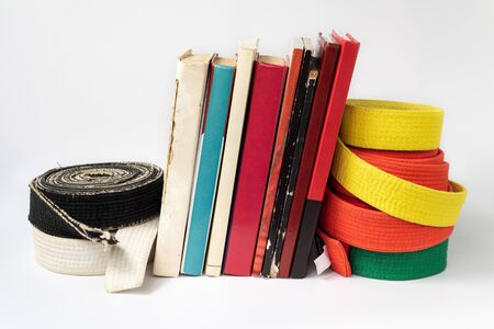 Black and white martial arts belt on a stack of books on the study of martial arts of aikido, karate, judo. Body and mind development.