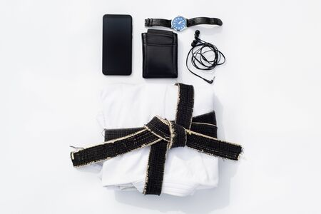 Martial arts. Aikido, Kendo or Iaido Classes Set. Blue hakama pants, phone, earphones and wallet and watch on a white background. Archivio Fotografico