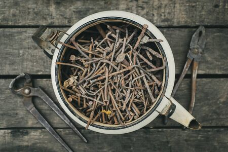 A pile of old metal, rusty nails in an iron teapot on a wooden table with pliers and nippers. Vintage still life. Archivio Fotografico
