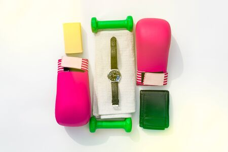 Brutal female fitness. Female sports equipment for martial arts. Pink gloves, green dumbbells, towel and watch on a white background.