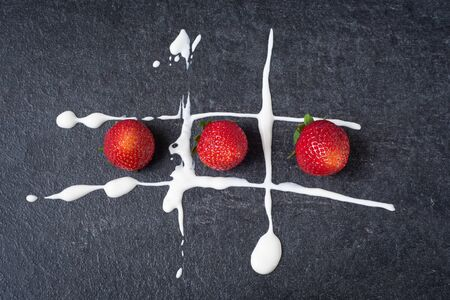 Red strawberry on a dark stone board with white sour cream. Game of tic tac toe with fresh berries. Stok Fotoğraf