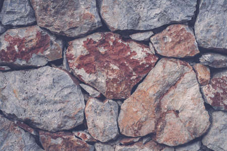 Modern wall of large unprocessed pieces of rock, stones. Background stone wall.