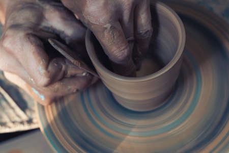 In the ceramics workshop. Beautiful hands of the master make peas on a potting wheel. Place for your text. Banque d'images