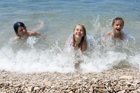 Children playing in the waves of sea photo