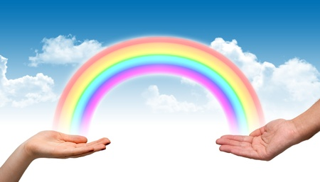 Male and female hand holding a rainbow Stock Photo
