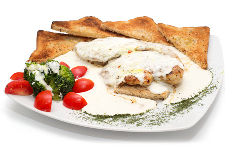 Chicken with gorgonzola, vegetables and bread on the plate photo