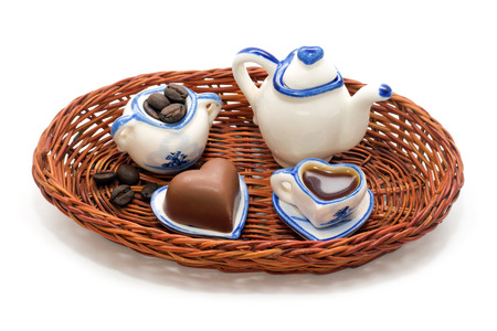 ewer: Miniature service for coffee, coffee beans and chocolate hearts in a wicker tray isolated on white background
