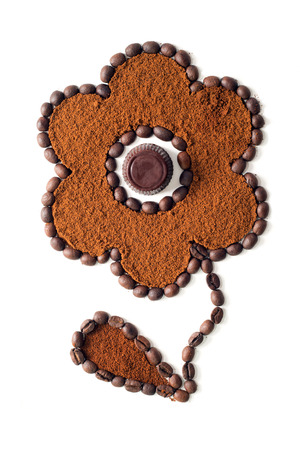 Flower made of coffee beans and ground coffee with chocolate candy in the middle isolated on white background  photo