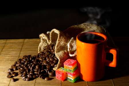 Coffee beans spilled out of the jute bag, orange cup of coffee and colorful jelly candies on wooden mat, black background and dim light  photo