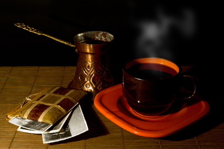 Cup of coffee, coffee pot and album with old photos on a wooden mat, black background and dim light  photo