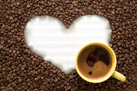White paper in heart shape with yellow cup of coffee on coffee beans background photo
