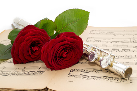 Silver flute and beautiful red rose on an ancient musical  photo