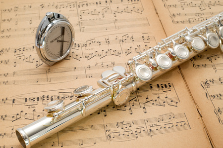 Silver flute and pocket metronome  on an ancient music score author of notes A Scriabin 1872-1915, Op 20 concert for the piano accompanied by second piano by N  Gilaiew, Moscow 1931 Stock Photo - 27712061