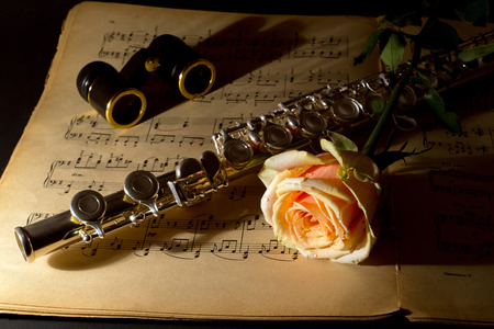 silver flute: Opera glasses, silver flute and yellow rose on an ancient music score author of notes S  Rachmaninoff 1873-1943, 24 preludes for the piano, publisher MUZGIZ 1946 , Moscow