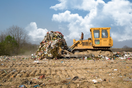 The old bulldozer moving garbage in a landfill  Imagens