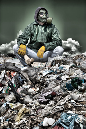 Man in a gas mask sitting on the garbage and holding a bone in his hand