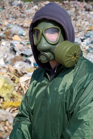 Man in a gas mask against polluted nature  photo