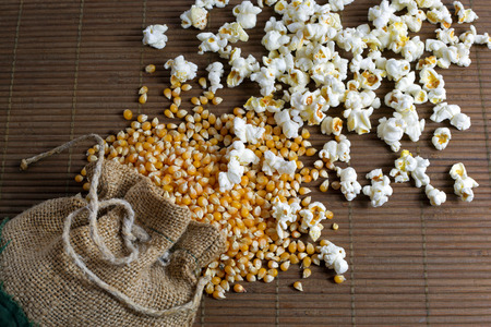 Popcorn spilled out of the jute bag over wooden background photo
