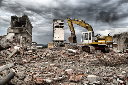 Bulldozer removes the debris from demolition of old derelict buildings photo