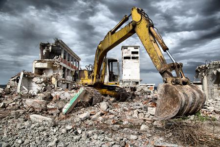 Bulldozer verwijdert het puin van de sloop van de oude vervallen gebouwen Stockfoto