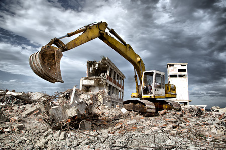 Bulldozer removes the debris from demolition of old derelict buildings Archivio Fotografico