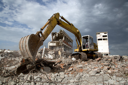 construction vehicle: Bulldozer removes the debris from demolition of old derelict buildings Stock Photo