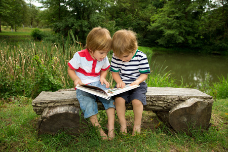Adorable Little Twin Brothers Sitting on a Wooden Bench and Reading a Book Very Carefully  Near the Beautiful Lake at Summer photo