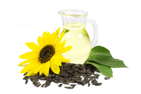 Sunflower and Seeds with Green Leaves and Sunflower Oil in Glass Pitcher Isolated on White Background  photo