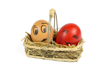 One Brown and One Red Egg with Funny Face in a Wicker Basket Isolated on White Background photo