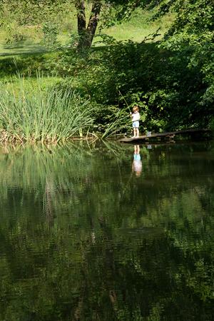 pescando: Pesca del ni�o peque�o desde el filo del Muelle de madera en el lago rodeado de naturaleza en verano