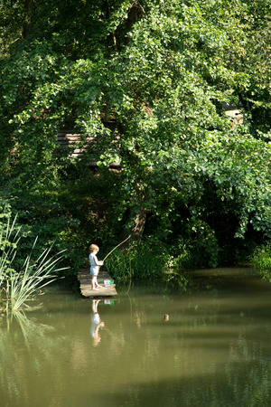 Little Boy Fishing from the Edge of Wooden Dock on Lake Surrounded by Beautiful Nature at Summer photo