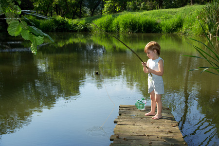 Cute Little Boy Fishing from the Edge of Wooden Dock and Patiently Waiting for his Catch in Sunny Summer Day photo