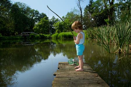 Adorable Little Boy Fishing from Wooden Dock on a Lake in Sunny Summer Day photo