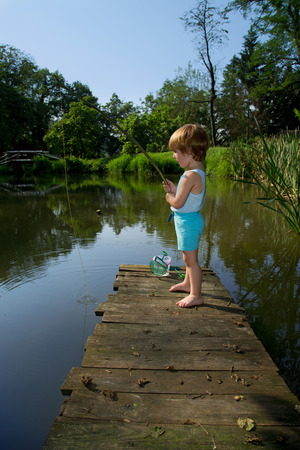 Sweet Little Boy Standing on the Edge of Wooden Dock and Fishing on  Lake in Sunny Summer Day photo