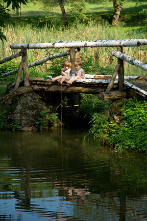 Adorable Little Twin Brothers Sitting on the Edge of Wooden Bridge and Fishing on Beautiful Lake at Summer photo
