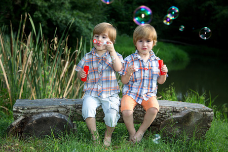 Little Twin Brothers Sitting on Wooden Bench and Blowing Soap Bubbles in Summer Park  photo