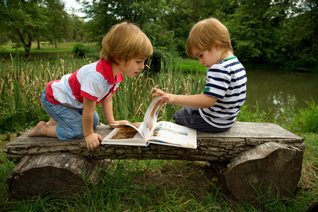 Adorable Little Twin Brothers Sitting on a Wooden Bench and Looking at Interesting Pictures in the Book Near the Beautiful Lake at Summer photo