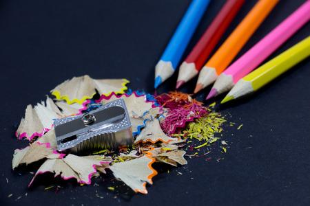 black metallic background: Sharpened Colorful Pencils Coming from Corner, Metallic Pencil Sharpener and Colorful Pencil Shavings on Black Background