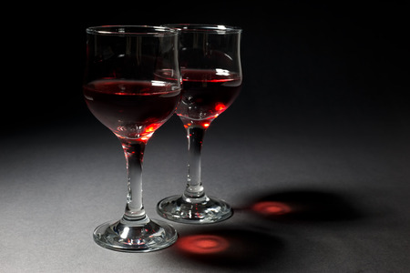Two Glasses of Red Wine and Their Interesting Reflection Over Black Background