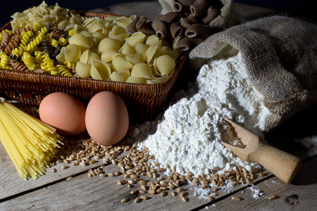 Wicker Basket Filled with Pasta of Different Colors and Shapes, Flour in Jute Bag and Two Eggs on Rustic Wooden Table Closeup photo
