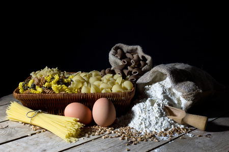 Wicker Basket Filled with Pasta of Different Colors and Shapes, Flour in Jute Bag and Two Eggs on Rustic Wooden Table Over Black Background photo