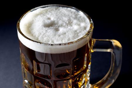 Becher frisches Bier mit Schaum über Schwarzem Hintergrund Nahaufnahme