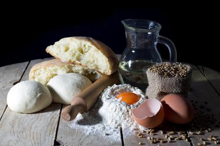 making bread: Naturaleza muerta con ingredientes para hacer pan en la mesa de madera sobre fondo Negro