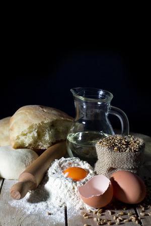 ferment: Still Life with Ingredients for Making Bread on Wooden Table Over Black Background