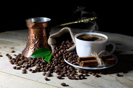 seeds coffee: Hot Black Coffee in Coffee Pot and White Coffee Cup with Coffee Beans on Black Background