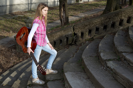 casually dressed: Pretty Young Girl Casually Dressed with Guitar in Her Hand Walking Up the Stairs in the Park on Sunny Day